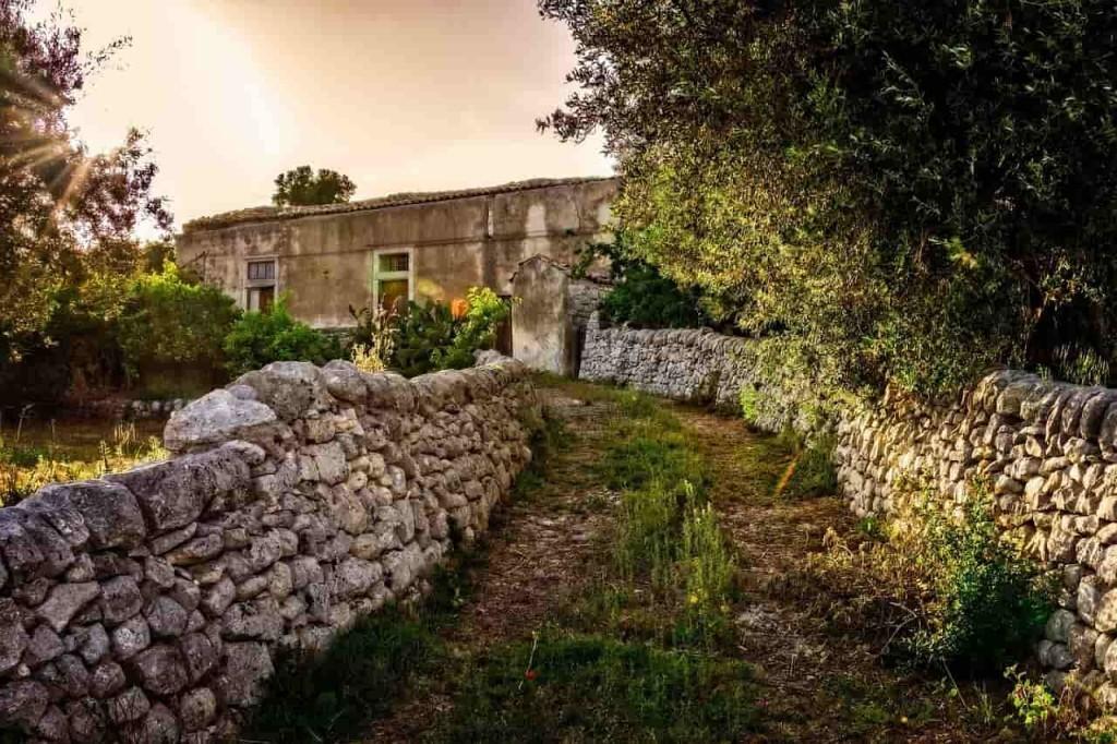 Дорога к дому с каменным забором
